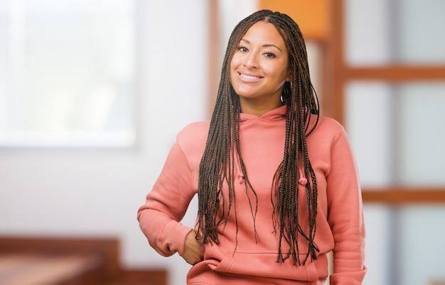Ritratto di una giovane donna nera che indossa le trecce allegro e con un grande sorriso