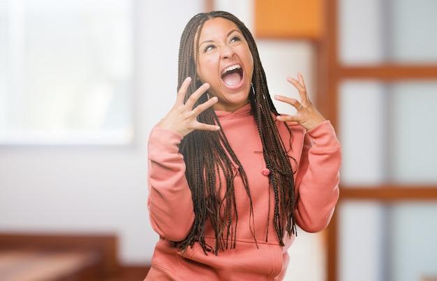 Ritratto di una giovane donna nera che indossa le trecce molto arrabbiato e sconvolto, molto teso