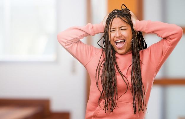 Ritratto di una giovane donna nera che indossa le trecce pazzo e disperato