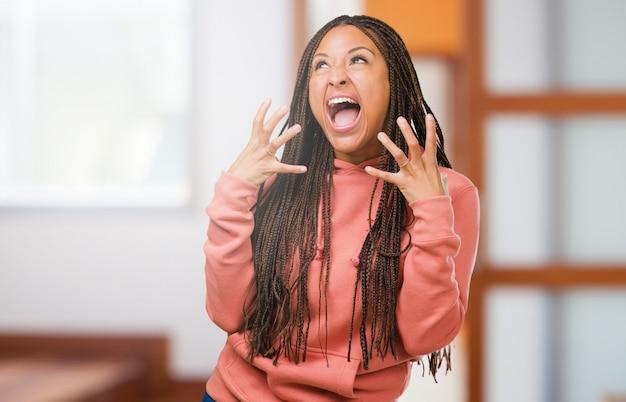 Ritratto di una giovane donna nera che indossa trecce molto arrabbiate e sconvolte, molto tese, urlanti furiose, negative e pazze