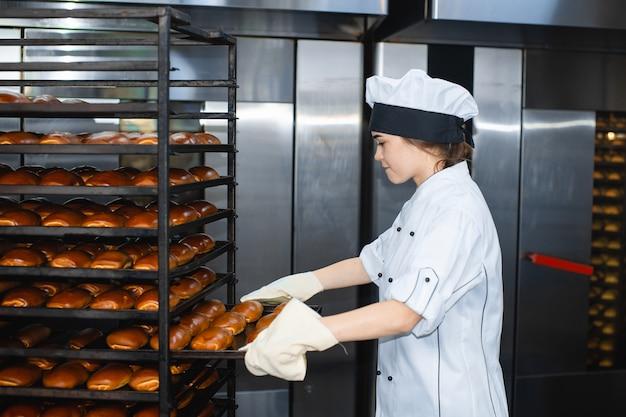 Ritratto di una giovane donna panettiere con forno industriale con pasticcini in un forno
