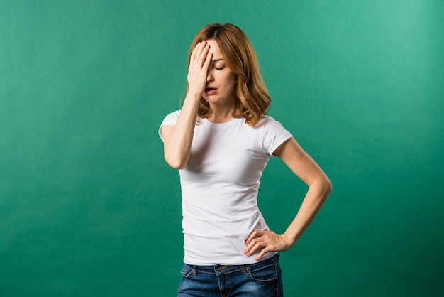 Ritratto di una giovane donna preoccupata contro sfondo verde