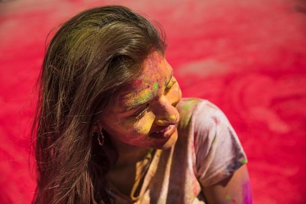Ritratto di una giovane donna ricoperta di polvere di holi guardando lontano