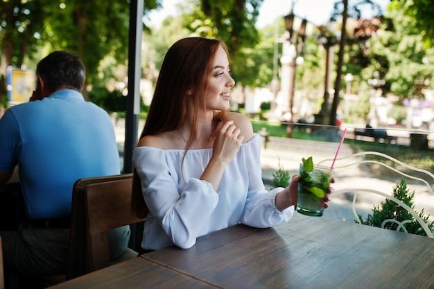 Ritratto di una giovane donna sbalorditiva che posa con il cocktail di mojito in caffè accanto al parco.