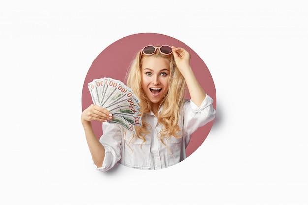 Ritratto di una giovane donna scioccata con un fascio di banconote e vendita di testo. fa capolino attraverso il buco bianco nel muro faccia buffa con la bocca aperta. wow concept