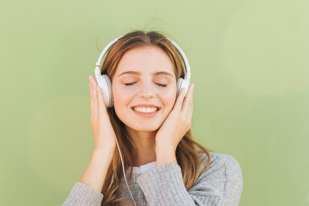 Ritratto di una giovane donna sorridente che ascolta la musica sulla cuffia con il suo occhio chiuso contro il fondo verde della menta