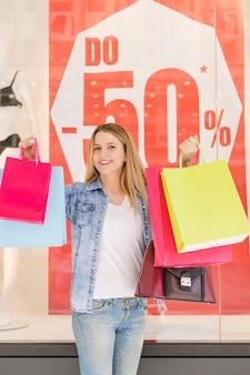 Ritratto di una giovane donna sorridente che tiene i multi sacchetti della spesa colorati