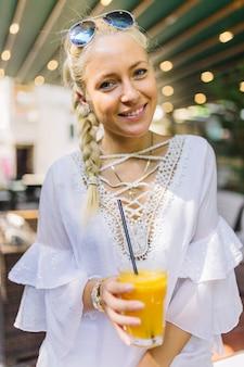 Ritratto di una giovane donna sorridente che tiene vetro di succo con cannuccia in esso