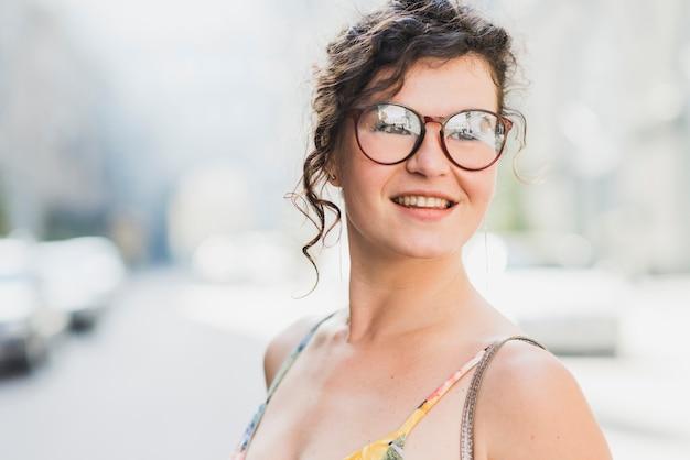 Ritratto di una giovane donna sorridente con gli occhiali