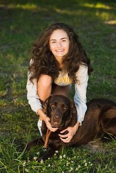 Ritratto di una giovane donna sorridente con il suo cane nel parco