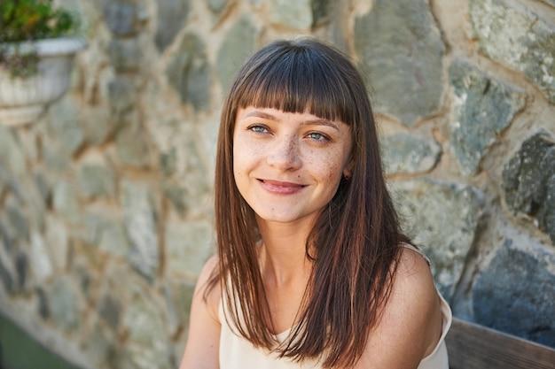 Ritratto di una giovane donna sorridente con le lentiggini sul viso in estate su una strada cittadina