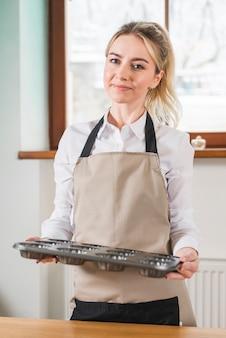 Ritratto di una giovane donna sorridente con vassoio vuoto cupcake