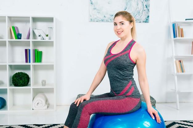 Ritratto di una giovane donna sorridente di forma fisica che si siede sulla palla blu dei pilates che esamina macchina fotografica