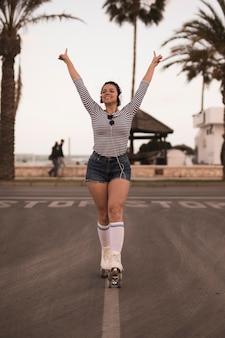 Ritratto di una giovane donna sorridente in piedi sulla strada alzando le sue mani ascolto musica in cuffia