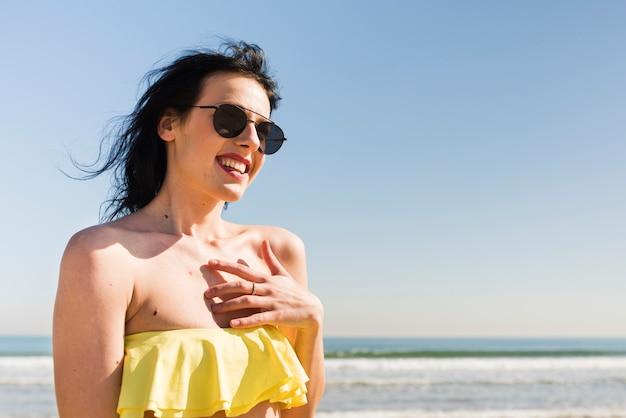 Ritratto di una giovane donna sorridente nella parte superiore di bikini che si leva in piedi contro il cielo blu alla spiaggia