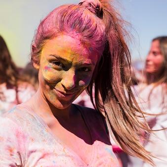 Ritratto di una giovane donna sorridente ricoperta di colore holi
