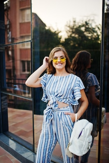 Ritratto di una giovane donna splendida nella posa globale e gialla a strisce degli occhiali da sole