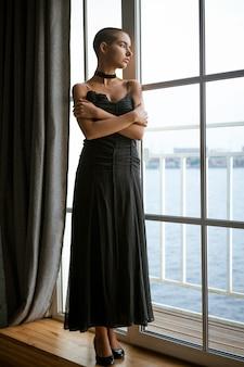 Ritratto di una giovane donna triste con i capelli corti in piedi guardando fuori dalla finestra in un abito nero.
