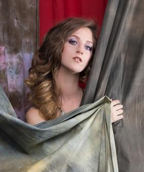 Ritratto di una giovane e bella donna bionda, chiusa da una tenda