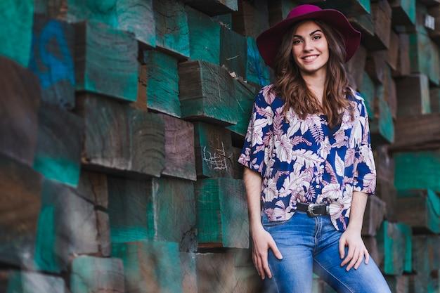 Ritratto di una giovane e bella donna che indossa abiti casual e un cappello moderno, in piedi su sfondo verde di blocchi di legno e sorridente. stile di vita all'aperto.