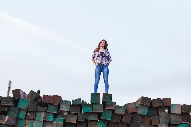 Ritratto di una giovane e bella donna che indossa abiti casual, in piedi su una montagna di blocchi di legno verde