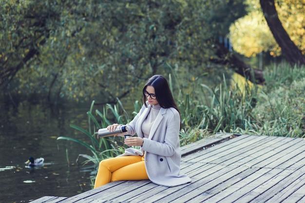 Ritratto di una giovane e bella donna che indossa un cappotto all'aperto