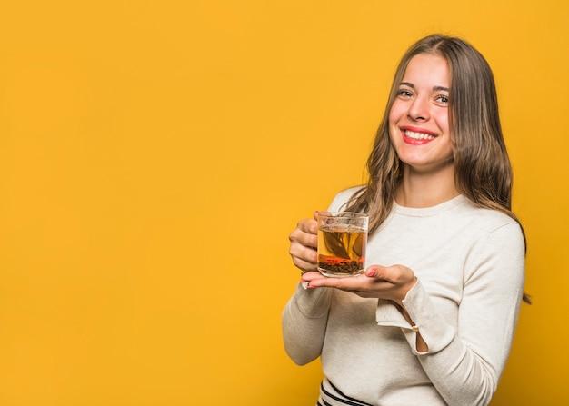 Ritratto di una giovane e bella donna che mostra tazza di vetro tisana contro sfondo giallo