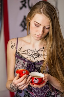 Ritratto di una giovane e bella donna con tatuaggio mehndi sul petto guardando la tazza di tè in porcellana in mano