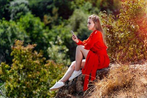 Ritratto di una giovane e bella donna in abito rosso, arancione. vista sul parco. vista lago sfondo sfocato. capelli lunghi. bel trucco. servizio fotografico professionale. avvicinamento.