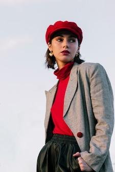 Ritratto di una giovane e bella donna in piedi davanti a cielo blu
