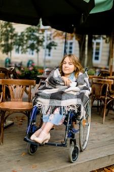 Ritratto di una giovane e bella donna su una sedia a rotelle, coperto di plaid a scacchi, bere caffè seduti in un caffè all'aperto.