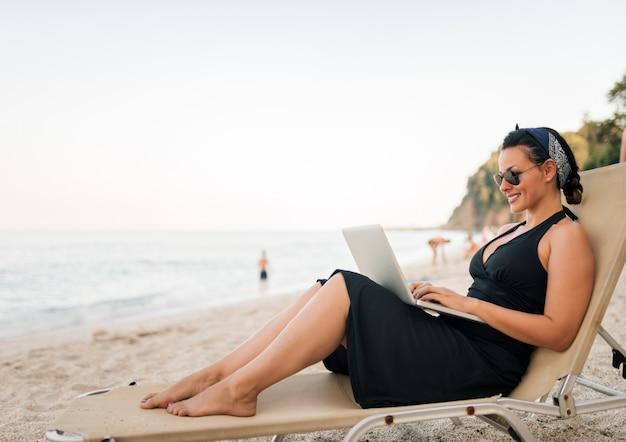 Ritratto di una giovane e bella donna usando il portatile sulla spiaggia.