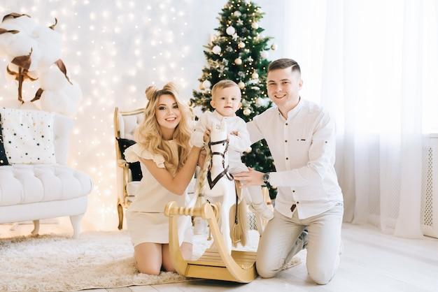 Ritratto di una giovane e bella famiglia sullo sfondo dell'albero di natale. la famiglia attraente celebra il nuovo anno, il bambino che cavalca un cavallo bianco e il sorriso dei genitori