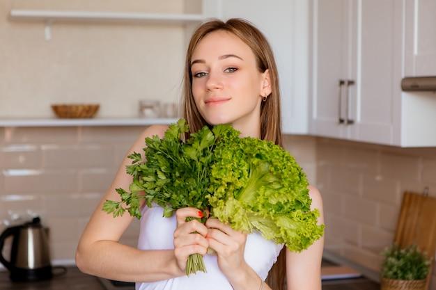 Ritratto di una giovane e bella ragazza con foglie di lattuga in cucina