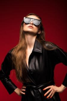 Ritratto di una giovane e bella ragazza in un cappotto di pelle nera su uno sfondo rosso.