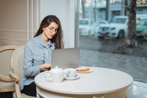 Ritratto di una giovane free lance femminile che utilizza un computer portatile per lavoro a distanza, mentre seduto in un moderno coffee shop interno, donna intelligente che lavora su net-book durante la colazione del mattino nel bar
