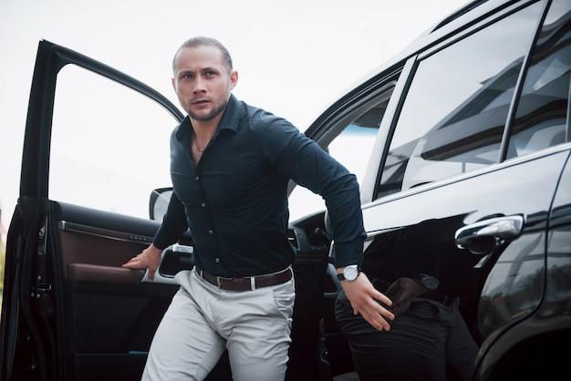 Ritratto di una giovane guardia del corpo vicino alla macchina. svolge lavori pericolosi