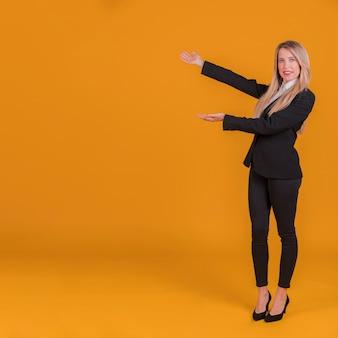 Ritratto di una giovane imprenditrice dando presentazione contro uno sfondo arancione