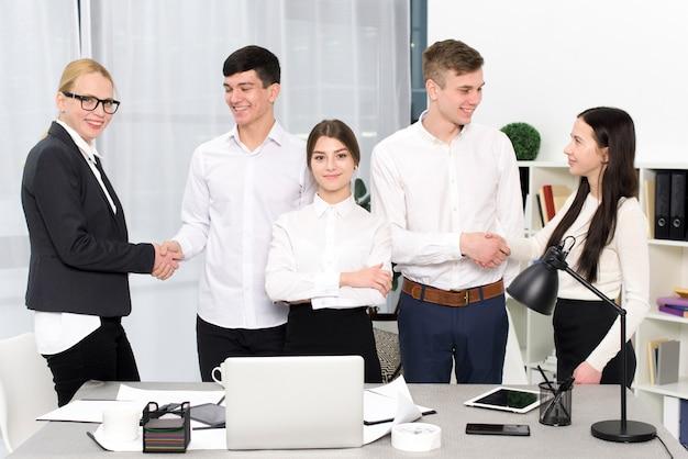Ritratto di una giovane imprenditrice in piedi con gli uomini d'affari si stringono a vicenda le mani sul posto di lavoro
