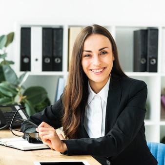 Ritratto di una giovane imprenditrice sorridente tenendo gli occhiali in mano guardando la fotocamera