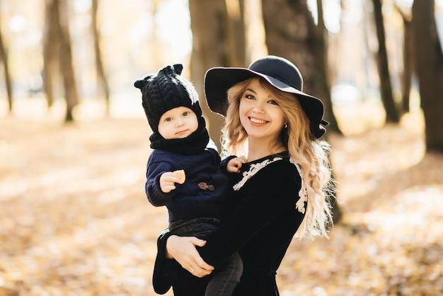 Ritratto di una giovane mamma elegante con bambini piccoli in autunno park.