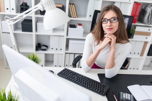Ritratto di una giovane ragazza a un computer scrivania in ufficio.