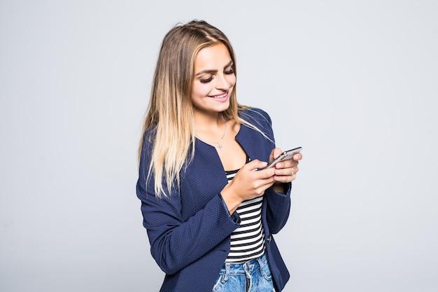 Ritratto di una giovane ragazza adolescente felice vestita in giacca utilizzando il telefono cellulare isolato