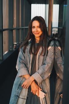 Ritratto di una giovane ragazza attraente emotiva vestita con un cappotto di jeans blu alla moda