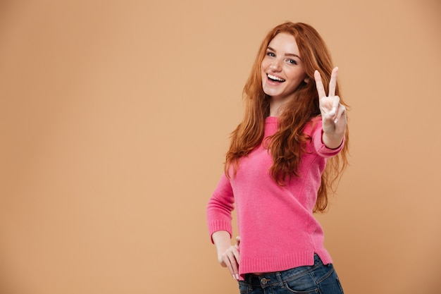 Ritratto di una giovane ragazza attraente rossa con gesto della mano vittoria