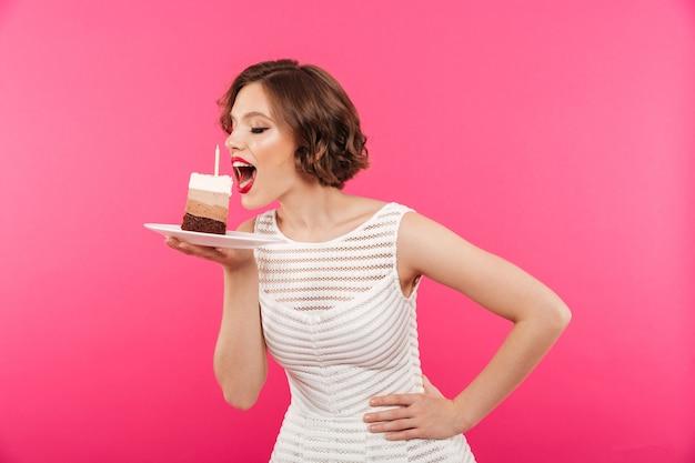 Ritratto di una giovane ragazza che mangia un pezzo di torta