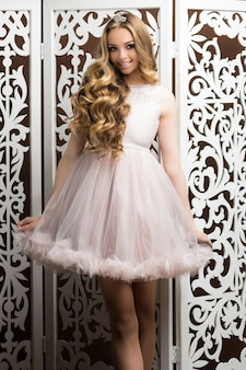 Ritratto di una giovane ragazza con lunghi capelli biondi in abito da principessa rosa