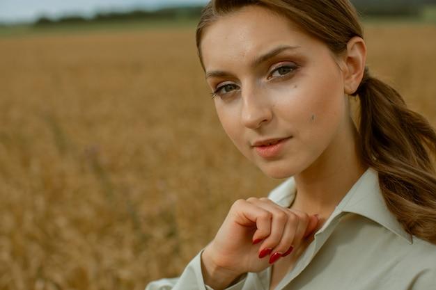 Ritratto di una giovane ragazza contro un campo giallo.