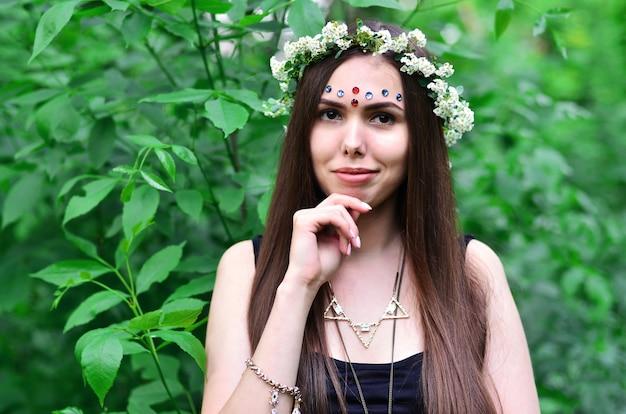 Ritratto di una giovane ragazza emotiva con una corona di fiori sulla sua testa