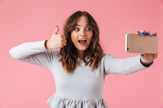 Ritratto di una giovane ragazza felice che cattura selfie cellulare